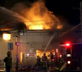Firefighters battle a blaze in a building on the Seaside Park boardwalk.