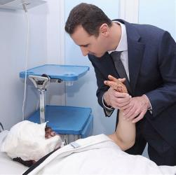 This undated photo posted on the official Instagram account of the Syrian Presidency and purports to show Bashar al-Assad visiting a patient at a military hospital in Damascus, Syria.