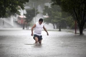 A man walks through a flooded street during heavy rains caused by Tropical Storm Ingrid in the Gulf port city of Veracruz, Mexico, yesterday.