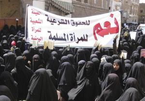 Yemeni women hold up the Quran and Arabic placard  reading yes to the legal rights of the Muslim woman as they take part in a protest outside the parliament in San'a, Sunday, March 21, 2010.