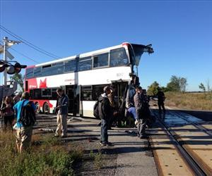 A city bus is severely damaged after colliding with a Via Rail passenger train at a crossing in Ottawa, Ontario, Wednesday, Sept. 18, 2013.