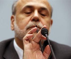 In this Wednesday, July 17, 2013, file photo, Chairman of the Federal Reserve Ben Bernanke taps the microphone, as he testifies before the House Financial Services Committee on Capitol Hill.
