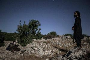 Syrian opposition fighters are seen at the top of a mountain in the vicinity of a rebel camp in Idlib province, Syria, Wednesday, Sept. 18, 2013.