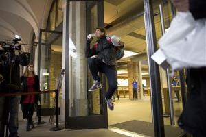 The second customer in line, Jesse Green, age 15, makes one of several jumps he repeatedly performed holding a boxed iPhone 5S upon leaving an Apple Store London, Friday, Sept. 20, 2013.
