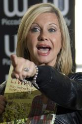 Australian actress Olivia Newton-John arrives at a central London bookstore for a signing of her book 'Livwise', Thursday, April 19, 2012.