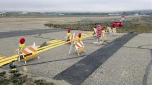 This Sept. 20, 2013 image provided by the Fairbanks International Airport shows the barricaded entrance to a taxiway, at Float Pond Road blocking access to Taxiway B in Fairbanks,  Alaska.
