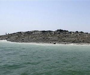 In this photo released by the Gwadar local government office on Wednesday, Sept 25, 2013, people walk on an island that reportedly emerged off the Gwadar coastline in the Arabian Sea.