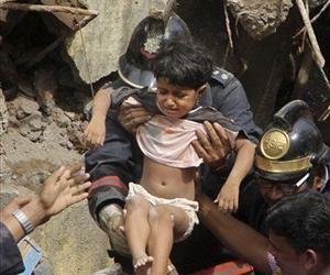 Indian Fire officials rescue a girl from the debris of a collapsed building in Mumbai, India, Friday, Sept. 27, 2013.