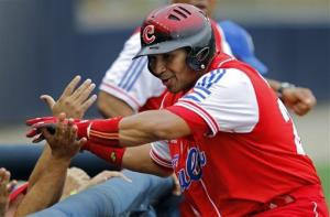 In this 2011 file photo, Cuba's Frederich Cepeda is congratulated by teammates after scoring during a Baseball World Cup game.
