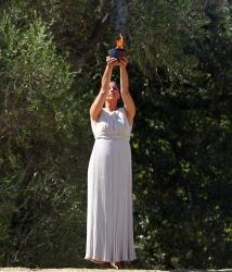 Actress Ino Menegaki, dressed as a high priestess, raises the Olympic Flame during a ceremony in Ancient Olympia, Greece, on Sunday, Sept. 29, 2013.