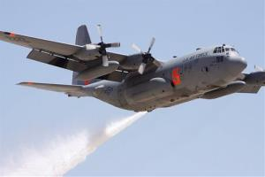 A Colorado Reserve C-130 drops water on a target during a certification flight at the Tucson International Airport in Tucson, Ariz.