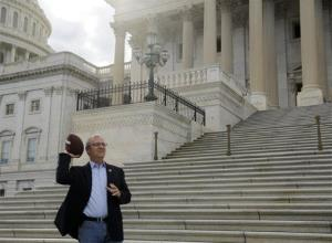 Rep. Kevin Cramer, R-Co., throws a football while waiting for to join other Republican House Members to call on Senate Democrats to come back to work yesterday.