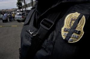 A piece of black tape covers the badge of a police officer in Tijuana, Mexico.