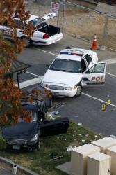 Capitol Hill police cars are seen behind the black car that set off today's chaos in DC.