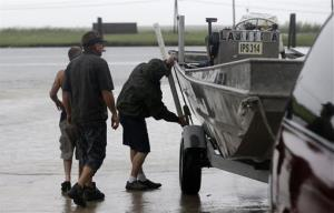 People put a boat in the water to secure their fishing camp in anticipation of Tropical Storm Karen at Myrtle Grove Marina in Plaquemines Parish, La.