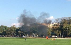 In this photo provided by Katy Scheflen, people run to a man who set himself on fire on the National Mall in Washington Friday.