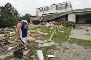 Travis Randall walks through the debris-strewn yard of his parent's home in Hickman, Neb.