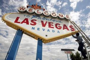 An electric company worker changing ballasts and lamps on the iconic Welcome to Las Vegas, sign in Las Vegas, Nev.