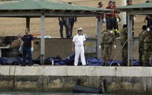 Italian soldiers and a Coast Guard officer stand next to body bags at the Lampedusa island, Italy, Sunday, Oct. 6, 2013, after the previous migrant boat capsized.