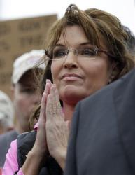 Tea Party activist and former Alaska Gov. Sarah Palin listens to a speaker at a rally at the World War II Memorial in Washington.