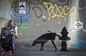 Graffiti by the secretive British artist Banksy, featuring a dog and a fire plug, draws attention on 24th Street, near Sixth Avenue in New York, on Friday, Oct. 4, 2013.