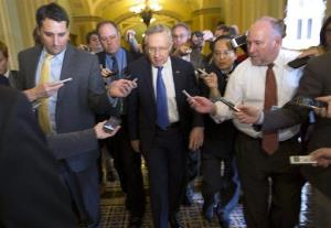 Senate Majority Leader Harry Reid is surrounded by reporters after leaving the office of Senate Minority Leader Mitch McConnell on Capitol Hill on Monday, Oct. 14, 2013.