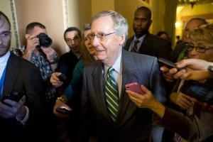 Senate Minority Leader Sen. Mitch McConnel is surrounded by reporters as he walks to the Senate floor on Monday.