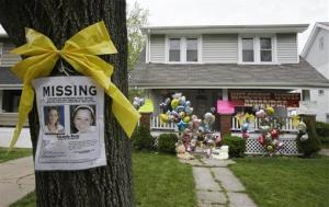 In this Wednesday, May 8, 2013 file photo, a missing poster still rests on a tree outside the home of Amanda Berry, in Cleveland.