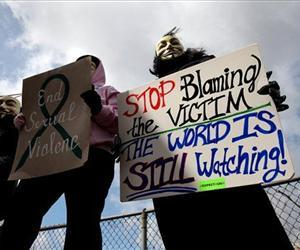 Protesters, who did not want to be identified, hold signs outside of the Jefferson County Justice Center and Jail in Steubenville, Ohio, on Wednesday, March 13, 2013.
