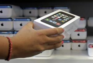 In this Friday, Sept. 20, 2013, file photo, a sales person pulls out an iPhone 5s for a customer during the opening day of sales of the iPhone 5s and iPhone 5C, in Hialeah, Fla.