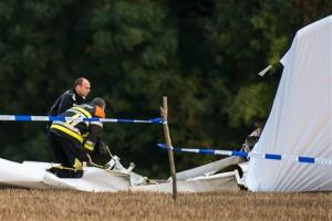 Rescue personnel work around the debris of a small plane which crashed in a field in Marchovelette, Belgium.