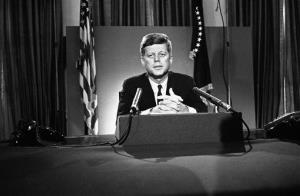 In this July 26, 1963 photo, President John F. Kennedy sits behind microphones at his desk in Washington after finishing a radio-television broadcast to the nation.