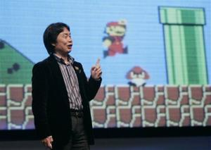 In this March 8, 2007 file photo, Shigeru Miyamoto, Nintendo Corp's top game designer, gives an address as the game Mario Brothers plays in background at the Game Developer Conference in San Francisco.