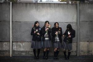 Students from a high school in Osaka, Japan, pose for private photos in front of the Berlin Wall.