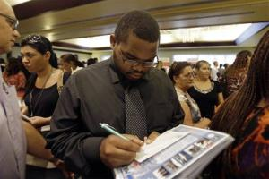 In this Wednesday, Aug., 14, 2013, file photo, job seeker Kelsey Devoe, of Miramar, Fla., fills out a contact form at a job fair in Miami Lakes, Fla.