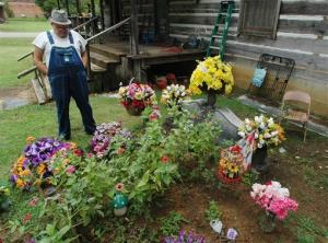James Davis, 73, stands over the grave of his wife, Patsy, in the front yard of the home they shared in Stevenson, Ala.