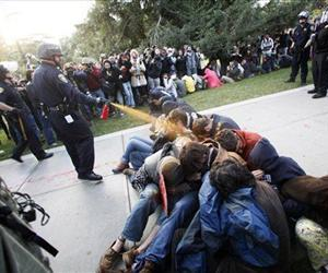 In this Nov. 18, 2011 photo, University of California, Davis Police Lt. John Pike uses pepper spray to move Occupy UC Davis protesters while blocking their exit from the school's quad in Davis, Calif.