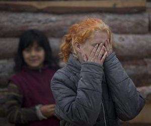 Minka Ruseva, daughter of Sasha Ruseva,  covers her face in a Roma neighborhood of Nikolaevo, Bulgaria, Friday, Oct. 25, 2013.
