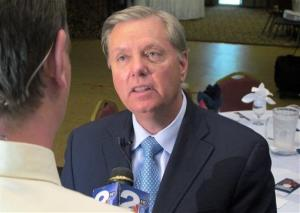In this Sept. 3, 2013, photo, U.S. Sen. Lindsey Graham talks to a reporter following a speech to business leaders in Goose Creek, SC.