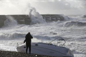 A boat lays stricken on the strand as people watch the waves batter into the sea wall of a marina in Brighton, south England, Monday, Oct. 28, 2013.