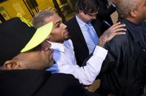Singer Chris Brown is surrounded by bodyguards as he departs the H. Carl Moultriel courthouse Monday, Oct. 28, 2013, with one of his attorneys, Danny Onorato, second from right, in Washington.