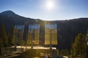 Three giant mirrors erected on the mountainside above the industrial town Rjukan, Norway, reflect sunshine toward the center of town.