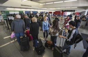 Departing passengers stand in line for check-in at Terminal 3 on Saturday, Nov. 2, 2013, in Los Angeles International Airport.