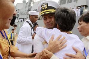 In this photo taken Dec. 3, 2010, navy officer Michael Vannak Khem Misiewicz embraces his aunt at a port in Cambodia.