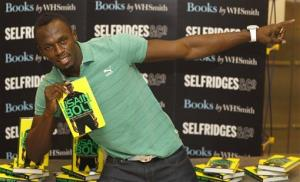 Jamaican athlete Usain Bolt poses for the media with a copy of his new autobiography called 'Faster than Lightning' at a department store in London, Thursday, Sept. 19, 2013.