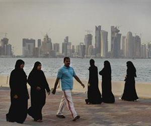 Qatari women and a man walk by the sea, Saturday, April 7, 2012, in Doha, Qatar.