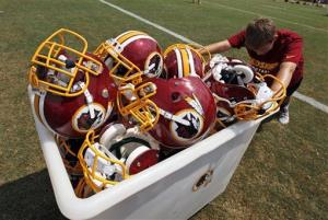 A Washington Redskins football team staff member wheels a bucket of helmets off the field after a practice at NFL football training camp at Redskins Park in Ashburn, Va.