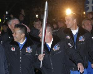 From  left, Japanese astronaut Koichi Wakata, Russian cosmonaut Mikhail Tyurin and US astronaut Rick Mastracchio walk to a bus with the Olympic torch.