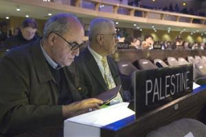 The Palestinian Ambassador to UNESCO, Elias Sanbar, left, checks his tablet during a session of the UNESCO General Conference, in Paris Friday, Nov. 8, 2013.