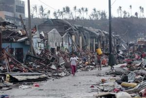 Residents walk past damaged structures caused by typhoon Haiyan,  in Tacloban city, Leyte province central Philippines on Sunday, Nov. 10, 2013.